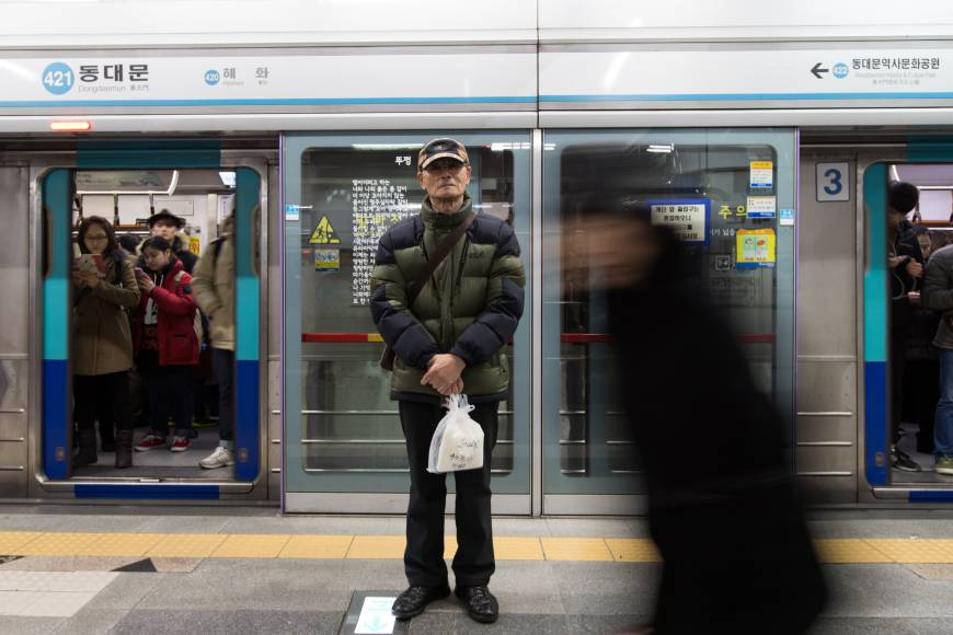Entregador, Cho Yong-moon, 75 anos de idade, carrega uma entrega na estação de metrô em Seul, Segunda-feira. / BLOOMBERG