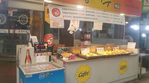 Um restaurante vende cerveja e camarão frito no Sinpo International Market. (Yonhap)