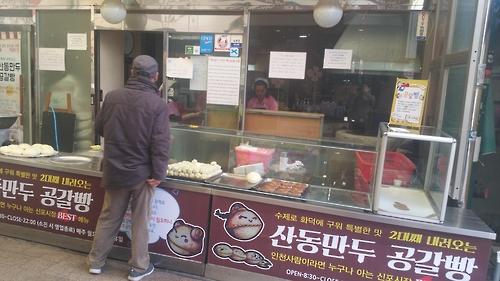 """Um homem compra um grande pão oco, ou """"gonggalbbang"""", no Sinpo International Market. (Yonhap)"""