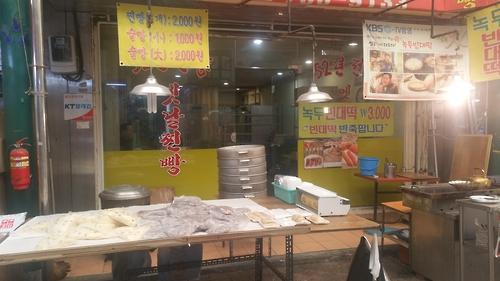 """Um restaurante vende bolos cozidos no vapor, ou """"jjinbbang"""", no Sinpo International Market. (Yonhap)"""