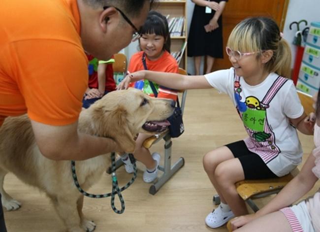 Dois cachorros foram convidados para a Unam Elementary School para uma aula destinada a aproximar os alunos dos animais, onde os estudantes abraçaram e deram apelidos aos cães, enquanto alguns ouviram seus batimentos cardíacos. Foto: Yonhap